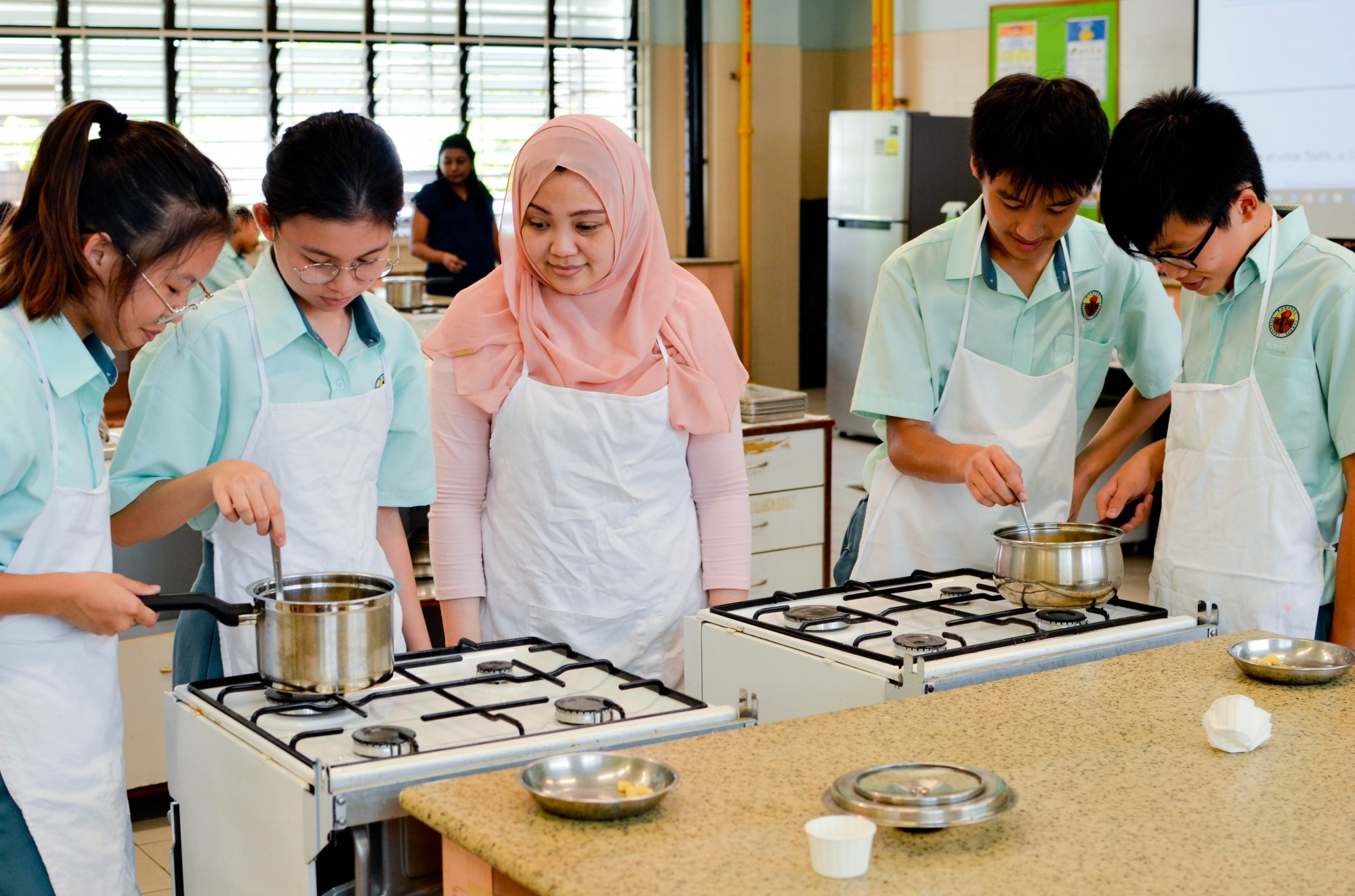 Teacher supervising students cooking..jpg